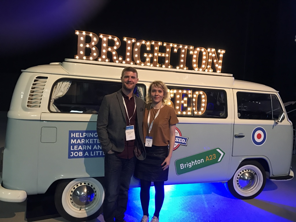 A man and woman in front of a BrightonSEO camper van.