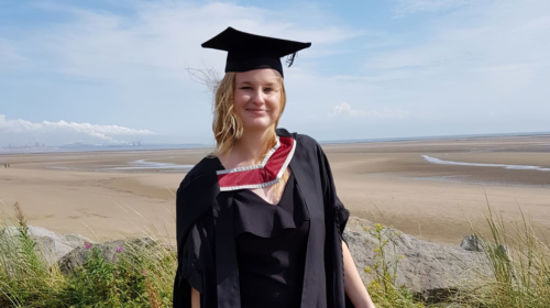 A woman in a graduation gown standing on a beach