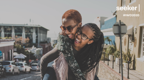 Two black women in glasses having a piggyback
