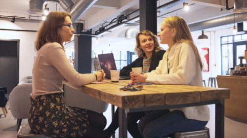 Three women sat around a table discussing how to get a site ready for link building